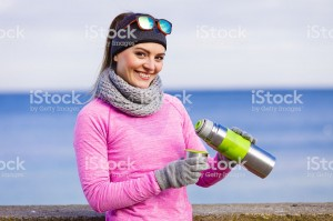Fit woman in cold day warming up drink tea