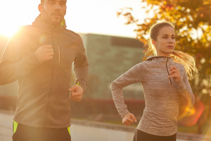 fitness, sport, people and lifestyle concept - couple running ou